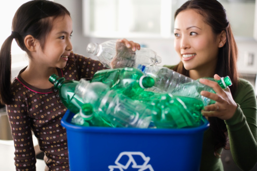 Mother and daughter with recycling bin